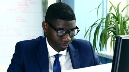 African American with glasses and a business suit carefully