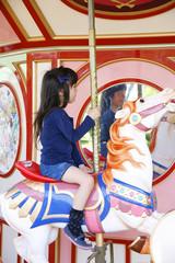メリーゴーランドに乗る女の子