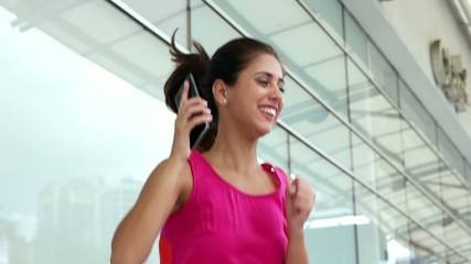 Young Woman On The Phone Jumping For Joy