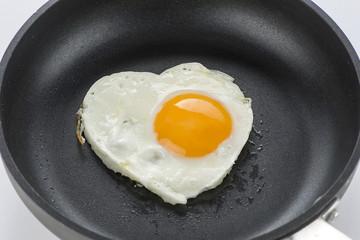 Heart made of fried egg on teflon pan.
