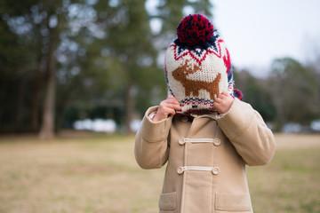 ニット帽を引っ張る少女