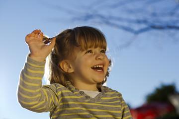 Niña pequeña saludando y riendo