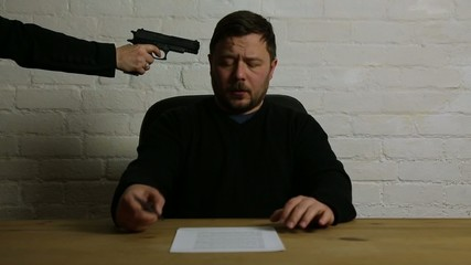 man signing contract at gun point of woman