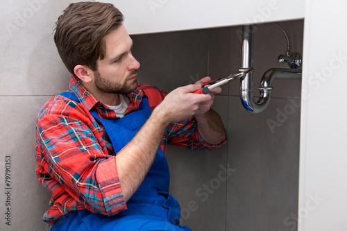 Leinwandbild Motiv Young plumber is repairing a sink at the bathroom