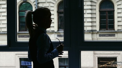 Businesswoman standing at the window after a busy day