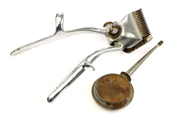 vintage metal hair trimmer and an oil can on a white background