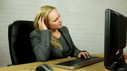 stressed blonde female boss typing at computer in office