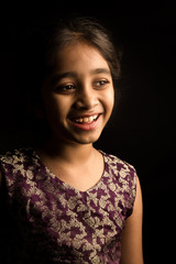Closeup portrait of happy indian girl isolated on black backgrou