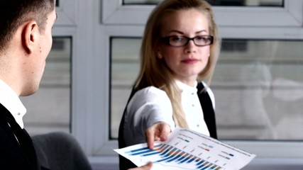 Blonde in glasses carrying on conversation with  colleague at