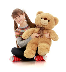 smiling girl sitting on the floor and hugging teddy bear