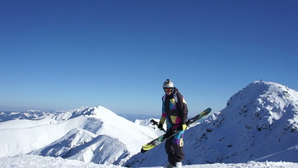 Man with skis standing on top of snowy mountain