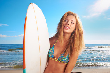 surfer girl posing with her surfboard