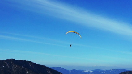 Colorful hang glider in sky over mountains