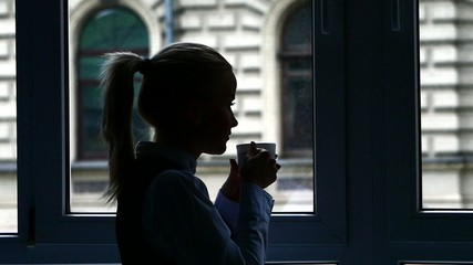Silhouette Businesswoman standing at the window after a busy day
