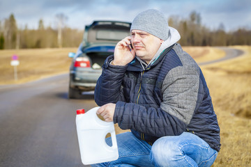 Man with cell phone and empty can waiting for help near car