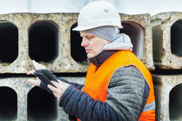 Civil engineer with tablet PC checking construction panels