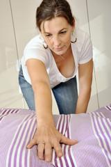 Frau bezieht Bett mit neuer Bettwäsche