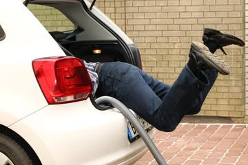 """Mann """"hängt"""" im Kofferraum PKW, reinigt, Sauger"""