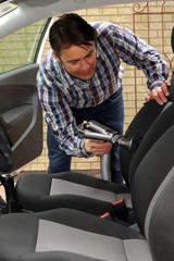 Autositzreinigung mit Autosauger, Mann reinigt