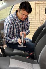 Mann reinigt PKW-Sitze mit Flachsaugeraufsatz