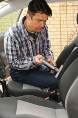 Mann reinigt mit Sauger den Beifahrersitz, PKW