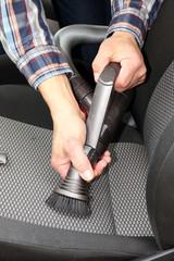 Autositz wird mit Bürstenaufsatz abgesaugt, PKW