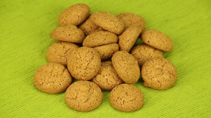 Amaretti biscuits rotate on a green background