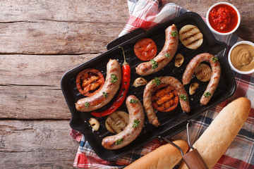 sausages with vegetables in a pan grill. horizontal top view