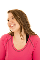 Young female model wearing a pink top glancing sideways smiling