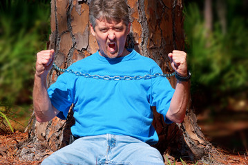Angry environmentalist protesting deforestation chained to tree