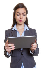Geschäftsfrau im grauen Blazer mit Tablet denkt nach