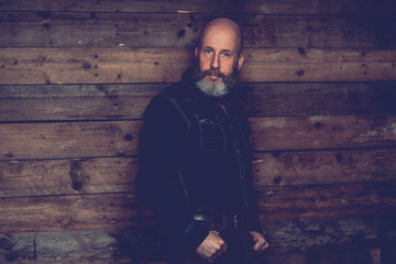 Bald Goatee Man Posing on Wooden Wall Background