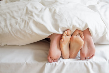 Two pairs of feet under the covers at home in bedroom