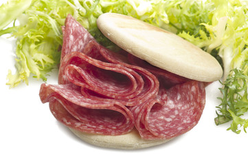 Salami sliced and bread with lattuce on white