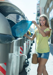 girl with rubbish near refuse  container