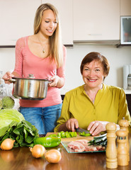 Happy mature woman with adult daughter cooking   at  kitchen