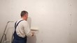 Home reconstruction: Senior man painting a wall in his apartment
