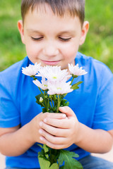 Boy holding flowers and smelling