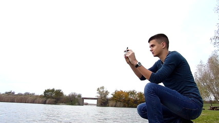 Young man taking photos with smart phone on lake shore