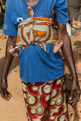 Mujer de raza negra llevando a su bebé encima.