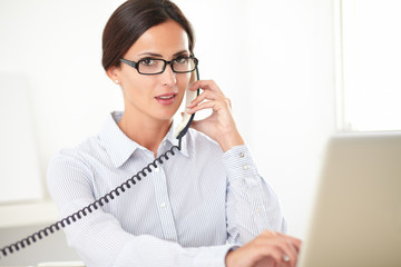 Pretty receptionist using the phone at workplace