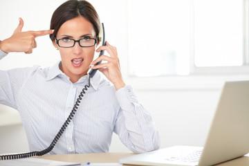 Young female secretary using the phone