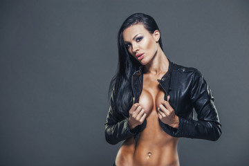 Beautiful girl sexy breasts in unbuttoned jacket with long black