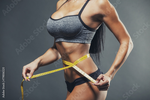 Woman measuring her waist with a yellow tape