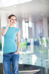 Pretty, young woman using her mobile phone/speaking on the phone