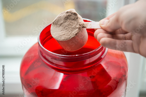 Man taking protein from container by the scoop. - 79808348