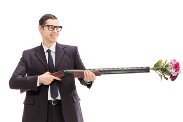 Businessman holding a rifle loaded with a bouquet of flowers