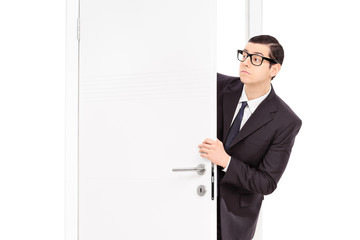 Businessman peeking through an opened door
