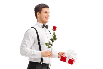 Elegant guy walking with a rose and a present