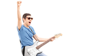 Enthusiastic young guitarist playing electric guitar